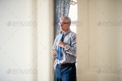Mature businessman on a business trip standing in a hotel room, getting dressed.