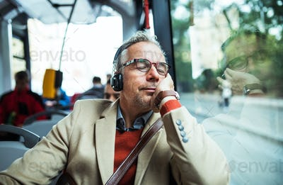 Mature tired businessman with heaphones travelling by bus in city.