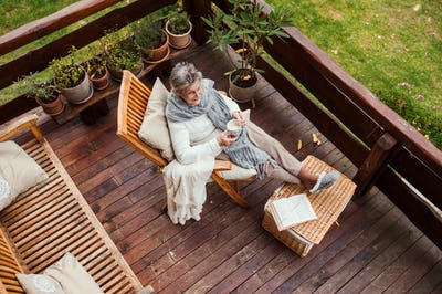 A top view of elderly woman with a book outdoors on a terrace in autumn.