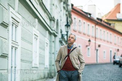 A mature businessman walking on a street in Prague city, hands in pockets.