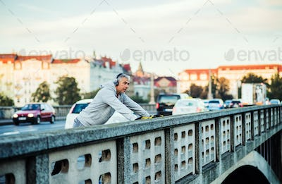 Mature male runner with headphones stretching outdoors on the bridge in Prague city.