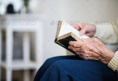 A close-up of senior woman reading Bible at home.