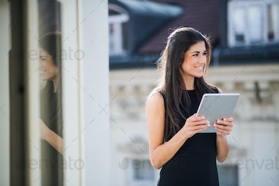 Young businesswoman with tablet standing on a terrace outside an office in city.