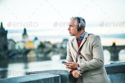 Mature businessman with headphones and smartphone standing by river in city.