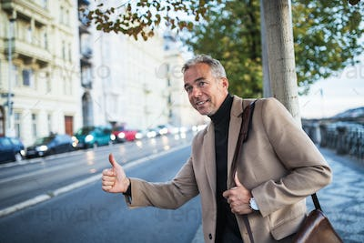 Mature businessman standing on the street in city, raising his hand to hail a taxi cab.