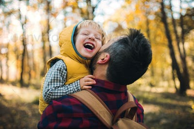 A mature father holding a toddler son in an autumn forest, having fun.