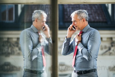 Mature businessman with smartphone standing on a terrace in city, making a phone call.