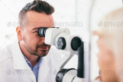 Optician checking his patient's eyes.