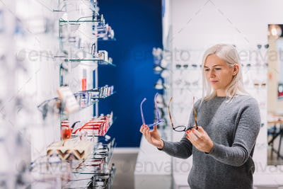 Woman comparing glasses at optic store.