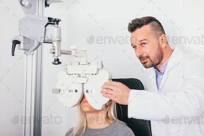 Optician checking woman's eyesight