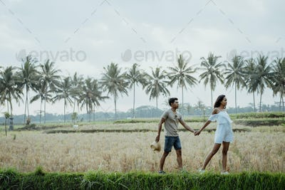 couple stylish walking in rice field together