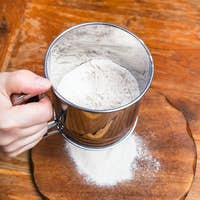 sifting the flour through sifter on wooden board