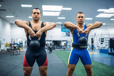 Strong male lifters doing exercise with kettlebell