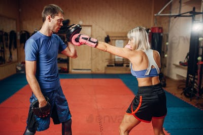 Female kickboxer on workout with personal trainer