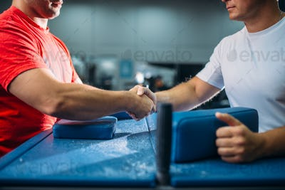 Two arm wrestlers shake hands after battle