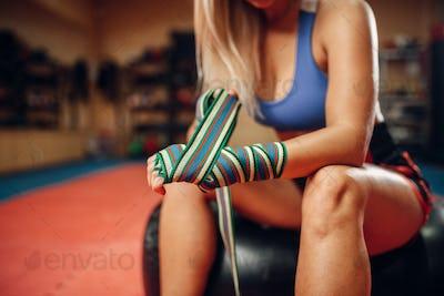 Female kickboxer sitting on punching bag in gym