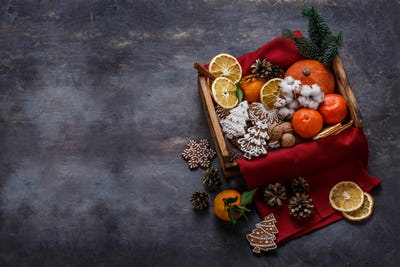 Christmas wooden box filled with gingerbread cookies, dry oranges, tangerines and nuts, copyspace