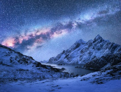 Bright Milky Way over snow covered mountains and sea bay at nigh
