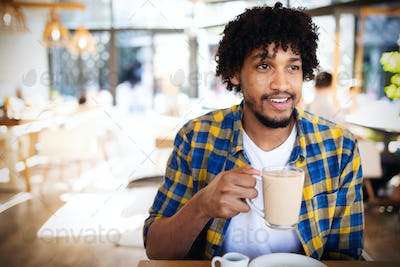 Handsome young african man drinking a cup of coffee at an cafe