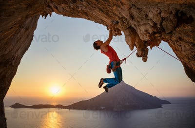 Male rock climber hanging with one hand on challenging route