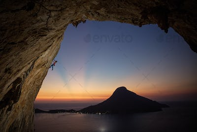 Male rock climber on overhanging cliff at sunset