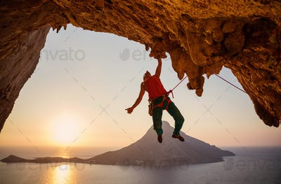 Male rock climber hanging on cliff with one hand at sunset