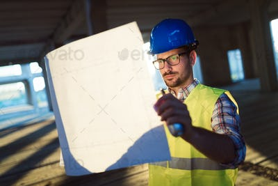 Male young architect with blueprints using walkie-talkie