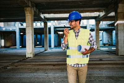 Male architect with blueprints using walkie-talkie