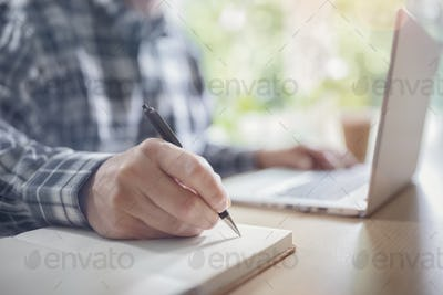 Businessman writing at desk in office with laptop computer