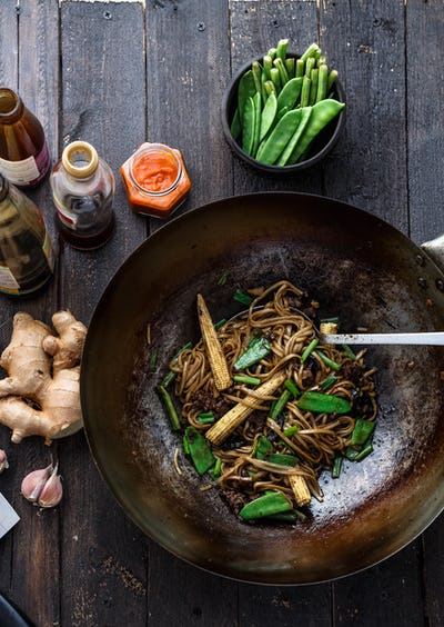 Stir-fried beef and noodles with oyster sauce in a wok, preparation process