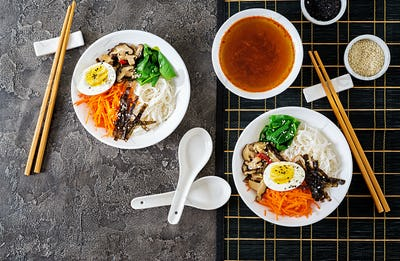 Diet vegetarian bowl of noodle soup of shiitake mushrooms, carrot and boiled eggs.