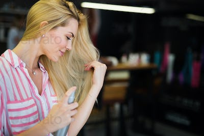 Woman fixes her hair with a hairspray