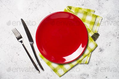 Red plate, cutlery and tablecloth on light stone table