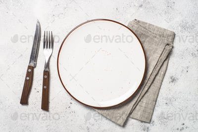 White craft plate, cutlery and napkin on white stone table