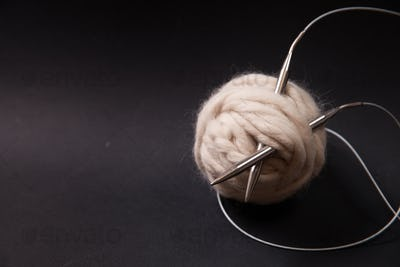 Yarn balls and sew needles on black background