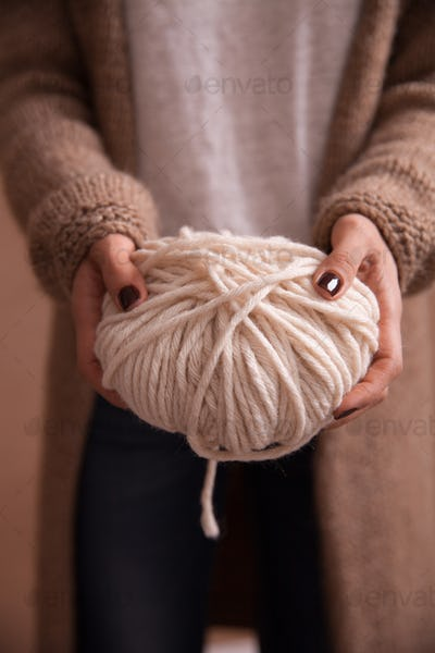 Close-up of yarn clew with knitting needles in female hands