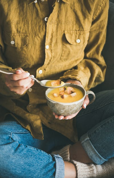 Woman sitting and eating pumpkin soup from mug