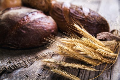 Rustic bread and wheat on an old vintage planked wood table. Dark moody