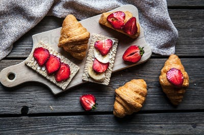 A delicious breakfast of strawberries and bread on wooden background. Fruit, food