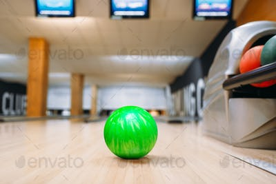 Green bowling ball on wooden floor in club