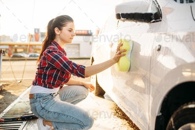 Young woman scrubbing vehicle with foam