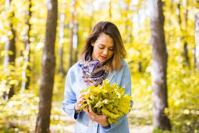 Fall, nature and people concept - Young beautiful woman in grey coat holding autumn bouquet of