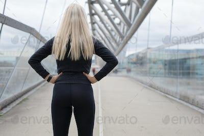 Fit blonde woman runner standing on bridge in modern looking city