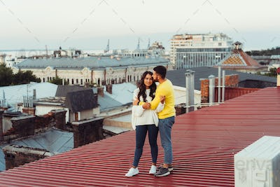 Loving young couple is standing on the roof of the house