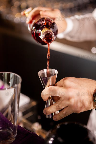 Closeup of bartender hands pouring alcoholic drink