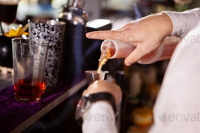 Barman in white shirt pouring drink incredient