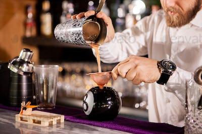 Bartender bartender is pouring a drink