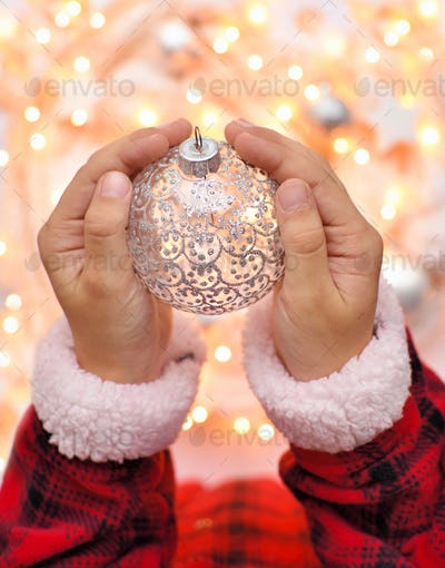 Christmas decoration ball in the children's hands against the ba