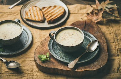 Warming celery cream soup and grilled bread over linen tablecloth