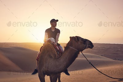 Camel riding in desert